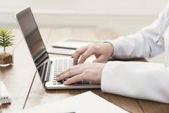 Close up das mãos do doutor no teclado do portátil imagens de stock royalty free