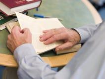 Close-up das mãos do estudante maduro que giram o livro Foto de Stock Royalty Free
