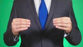 Close-up das mãos do homem de negócios que vestem o terno formal algo esticou através da largura da tela que realiza no seu vídeos de arquivo
