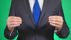 Close-up das mãos do homem de negócios que vestem o terno formal algo esticou através da largura da tela que realiza no seu video estoque