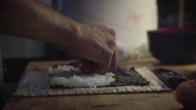 Close-up das mãos do homem que fazem um sushi video estoque
