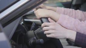 Close-up das mãos do pai e da filha que sentam-se atrás da roda de um carro luxuoso O pai ensina a menina conduzir video estoque