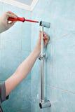Close-up das mãos do reparador montadas no bracke do chuveiro do suporte da parede Fotografia de Stock Royalty Free