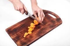 Close up das mãos do ` s do cozinheiro da mulher, cortando a cenoura em uma placa de madeira, isolada no fundo branco Fotografia de Stock