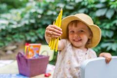 Close up das mãos do ` s da menina do litlle com lotes de lápis amarelos Foto de Stock