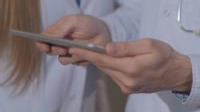 Close-up das mãos do ` s do doutor, considerando o cardiograma paciente do ` s na tabuleta vídeos de arquivo