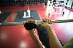 Close up das mãos do treinamento do homem novo com o instrutor da aptidão que usa o barbell no gym imagem de stock royalty free