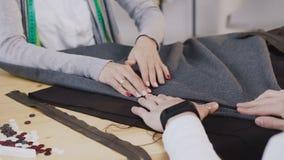 Close-up das mãos dos desenhadores de moda costurados que trabalham com materiais, eles que sentam-se na oficina bonita com video estoque