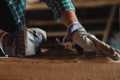 Close-up das mãos dos homens em luvas de trabalho com uma madeira cortada plana da mão woodworking, telhado, construção, fundo in imagens de stock royalty free