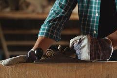 Close-up das mãos dos homens em luvas de trabalho com uma madeira cortada plana da mão woodworking, telhado, construção, fundo in imagem de stock royalty free