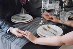 Close up das mãos dos pares na tabela do restaurante com dois vidros do champanhe Pares românticos que guardam-se mão do ` s em foto de stock royalty free