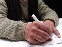 Close up das mãos enrugadas de uma pena e de um papel caucasianos velhos de terra arrendada do homem Foto de Stock Royalty Free