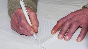 Close up das mãos enrugadas de uma pena e de um papel caucasianos velhos de terra arrendada do homem Fotografia de Stock