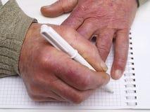 Close up das mãos enrugadas de uma pena e de um papel caucasianos velhos de terra arrendada do homem Fotos de Stock