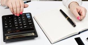 Close-up das mãos fêmeas com calculadora, pena de fonte e noteb Fotografia de Stock Royalty Free