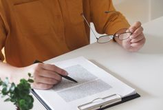 Close-up das mãos fêmeas escrevendo algo e guardar vidros em seu escritório foto de stock royalty free