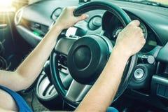 Close up das mãos fêmeas no volante no carro Humor do curso e da estrada do conceito Imagem de Stock