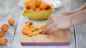 Close-up das mãos fêmeas que cortam abricós com uma faca em uma placa de corte Cozinhando o alimento do vegetariano vídeos de arquivo