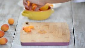 Close-up das mãos fêmeas que cortam abricós com uma faca em uma placa de corte Cozinhando o alimento do vegetariano filme