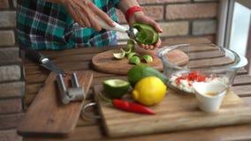 Close up das mãos fêmeas que cortam o abacate para o guacamole na tabela na cozinha home filme