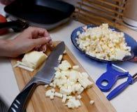 Close-up das mãos fêmeas que descascam e que desbastam maçãs na placa de corte de bambu na tabela na cozinha imagem de stock royalty free