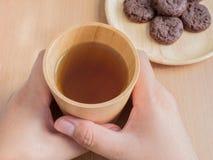 Close up das mãos fêmeas que guardam o copo de madeira de Jasmine Tea orgânico com cookies Fotografia de Stock Royalty Free