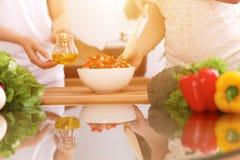 Close up das mãos humanas que cozinham na cozinha Mãe e filha ou dois amigos fêmeas que cortam vegetais para a salada fresca Imagem de Stock Royalty Free