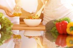 Close up das mãos humanas que cozinham na cozinha Mãe e filha ou dois amigos fêmeas que cortam vegetais para a salada fresca Fotografia de Stock Royalty Free