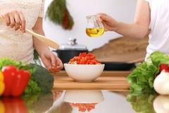 Close up das mãos humanas que cozinham na cozinha Mãe e filha ou dois amigos fêmeas que cortam vegetais para a salada fresca Imagem de Stock