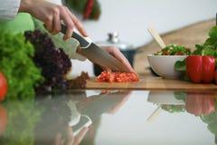 Close up das mãos humanas que cozinham a salada dos vegetais na cozinha na tabela de vidro com reflexão Foto de Stock Royalty Free
