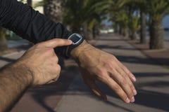 Close up das mãos masculinas com relógio do esporte imagens de stock