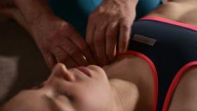 Close-up das mãos masculinas do fisioterapeuta que fazem a massagem do bem-estar a um paciente da moça Osteopathy e não tradicion filme