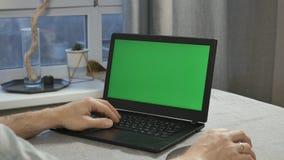 Close-up das mãos masculinas que funcionam em um portátil com uma tela verde vídeos de arquivo