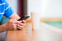 Close up das mãos masculinas que guardam o telefone celular e a classe de cofee no café Homem que usa o smartphone móvel Imagem de Stock Royalty Free