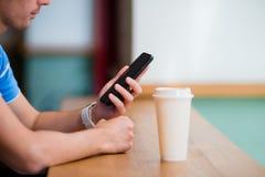 Close up das mãos masculinas que guardam o telefone celular e a classe de cofee no café Homem que usa o smartphone móvel Fotografia de Stock Royalty Free