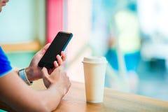 Close up das mãos masculinas que guardam o telefone celular e a classe de cofee no café Homem que usa o smartphone móvel Menino q Imagens de Stock Royalty Free