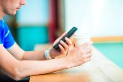 Close up das mãos masculinas que guardam o telefone celular e o vidro do café no café Homem que usa o smartphone móvel Menino que Imagem de Stock Royalty Free