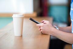 Close up das mãos masculinas que guardam o telefone celular e o vidro do café no café Homem que usa o smartphone móvel Menino que Fotos de Stock