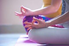 Close up das mãos das mulheres na ioga da prática do gesto do mudra interna Foto de Stock