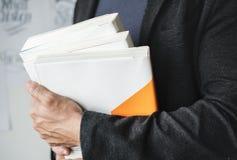 Close up das mãos que guardam a pilha de livros Fotos de Stock