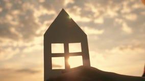 Close-up das mãos que guardam um modelo de papel em casa em um campo no por do sol Silhueta de uma casa de papel nos raios do filme