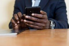 Close up das mãos que guardam um telefone celular imagens de stock