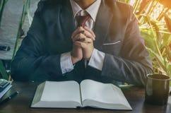 Close up das mãos que rezam na Bíblia imagem de stock royalty free