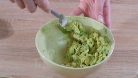 Close-up das m?os da mulher que trituram o abacate com a forquilha na bacia vídeos de arquivo