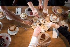 Close up das m?os multirraciais com sobremesas e copos de caf? em um caf? imagens de stock royalty free