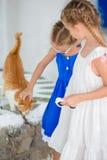 Close up das meninas adoráveis pequenas que afagam um gato vermelho na vila grega, Mykonos, Grécia, Europa Imagens de Stock Royalty Free
