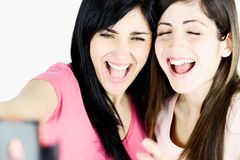 Close up das meninas que riem que toma a imagem com telefone esperto imagens de stock