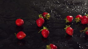Close-up das morangos em uma superfície molhada do preto filme