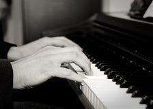 Close-up das mãos de homem novo que jogam um piano Imagem de Stock