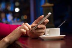 Close-up das mãos fêmeas que guardam um telefone celular Fotografia de Stock